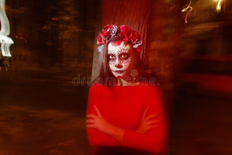 Oskarp kropp och röd lykta med en målad framsida av ett skelett en död levande död, i staden under dagen anda för dag allra, dag  royaltyfri foto