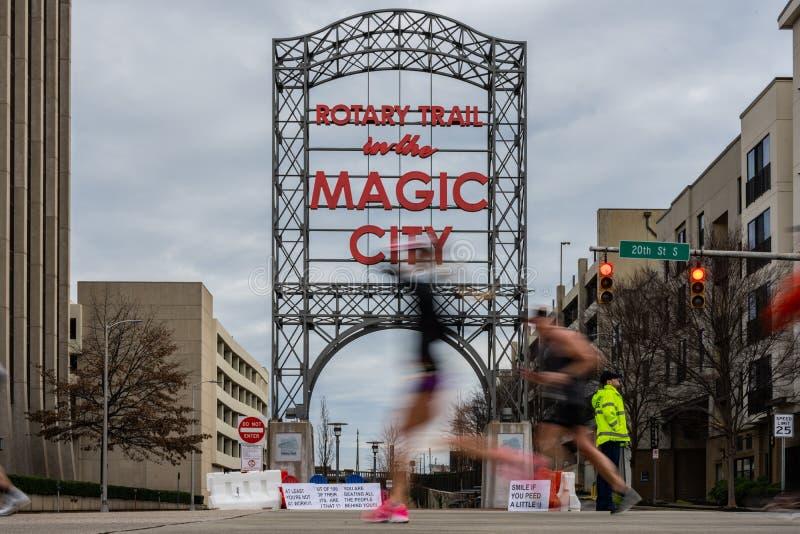 Oskarp löpare i rosa skon som kör tidigare Magic City-tecken arkivbild