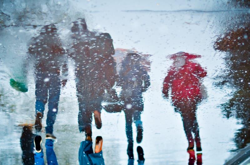 Oskarp reflexion i en pöl av fyra gå personer på den våta stadsgatan under regn och snö Lynnebegrepp royaltyfri bild