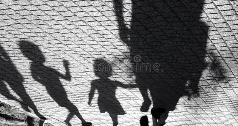 Oskarp skugga av lite pojken och en flicka som går med vuxna människor royaltyfria foton