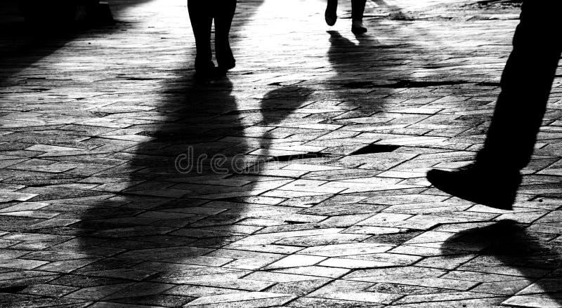 Oskarpa benkonturer och skuggor av folk som går i solnedgång arkivbilder