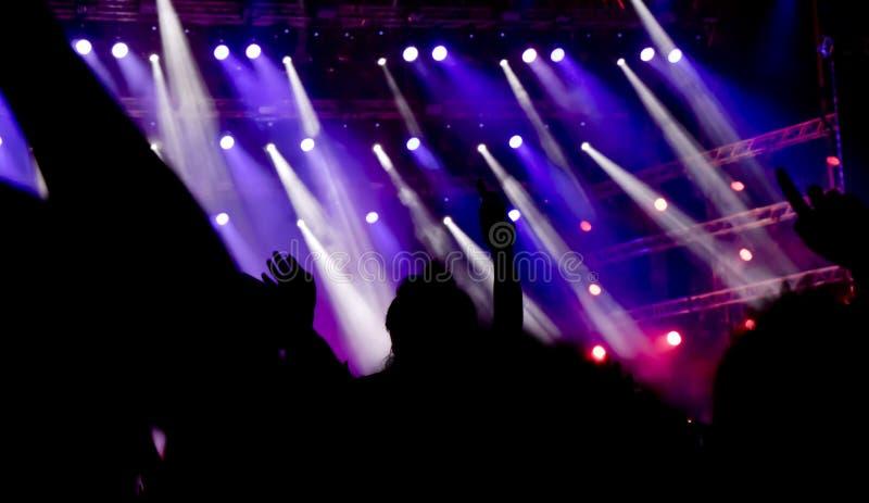 Oskarpa konturer av folk med lyftta händer på konserten royaltyfria foton