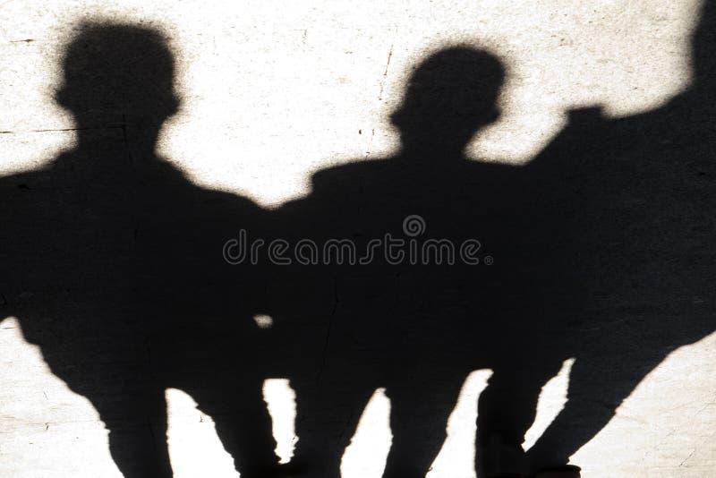 Oskarpa konturer och skuggor av tre personer som går stadsstre arkivfoton