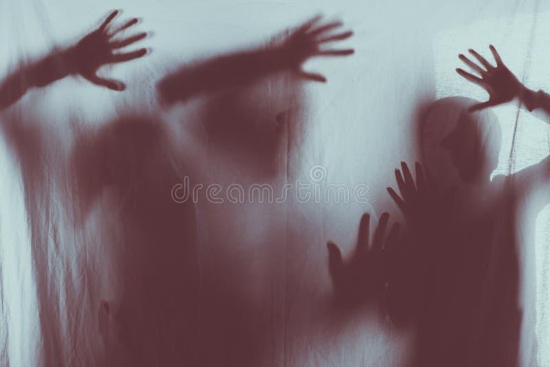 oskarpa läskiga konturer av folk som trycker på frostat exponeringsglas med händer arkivfoton