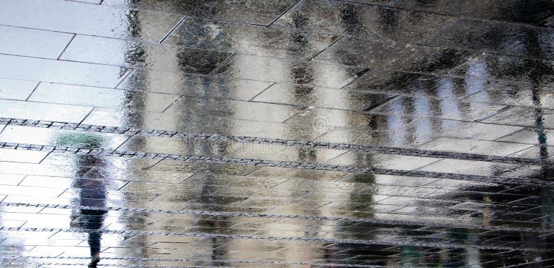 Oskarpa reflexionsskuggakonturer av en kvinna som bara går under paraplyet i regnet arkivfoto