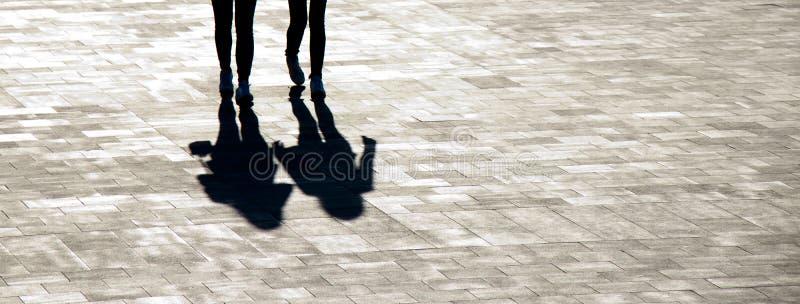 Oskarpa skuggakonturer av att gå för två unga kvinnor royaltyfri bild