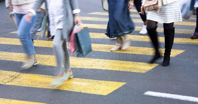 Oskarpt folk på gul zebramarkering arkivfoto