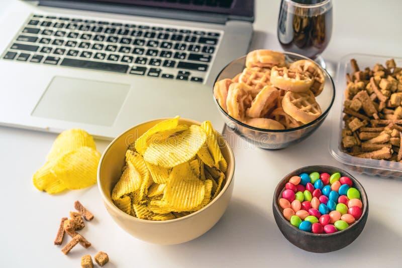 Oskick Arbetsutrymme med b?rbara datorn, godisar, chiper, cola p? vit bakgrund royaltyfri foto