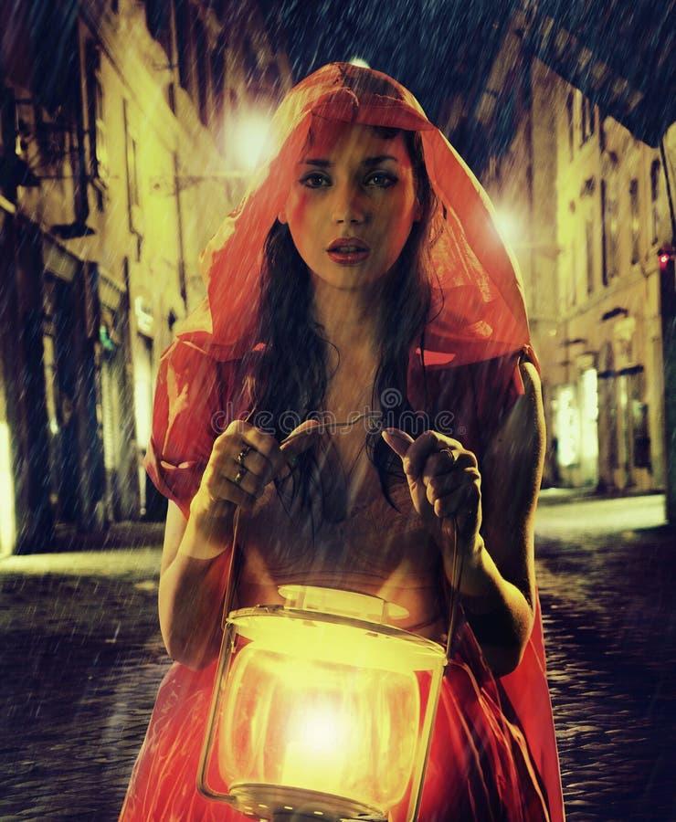 Oskyldig kvinna i rött innehav lyktan arkivfoton