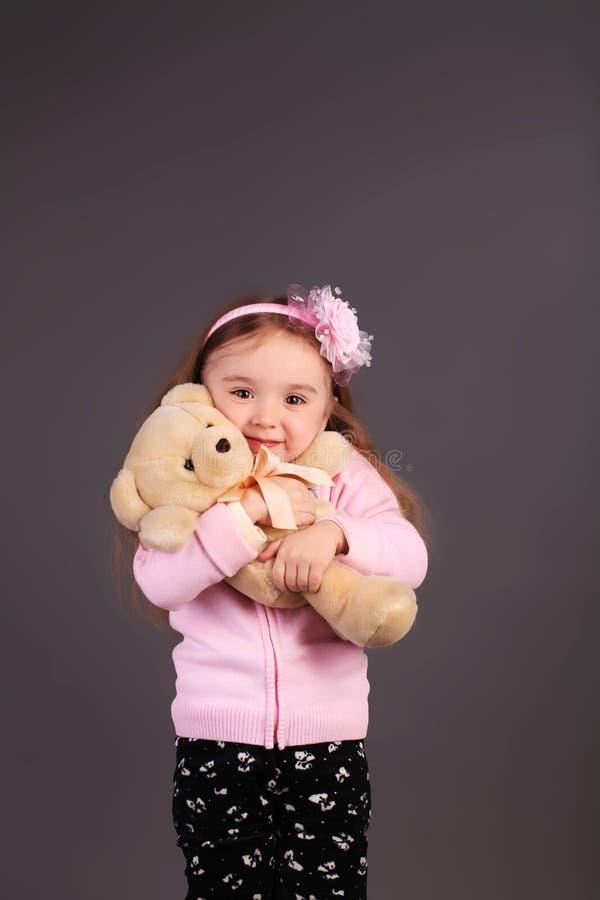 Oskyldig liten flicka som spelar med en björn royaltyfri foto