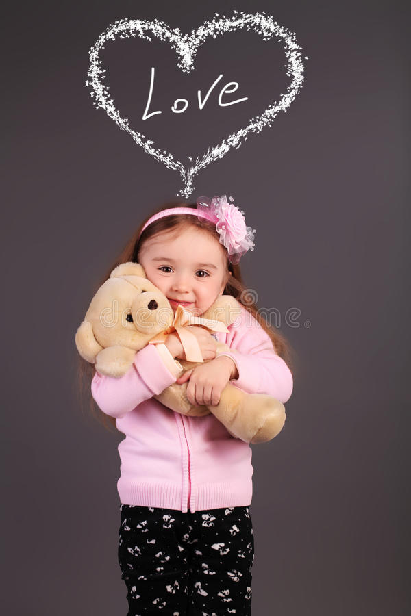 Oskyldig liten flicka som spelar med en björn arkivbilder