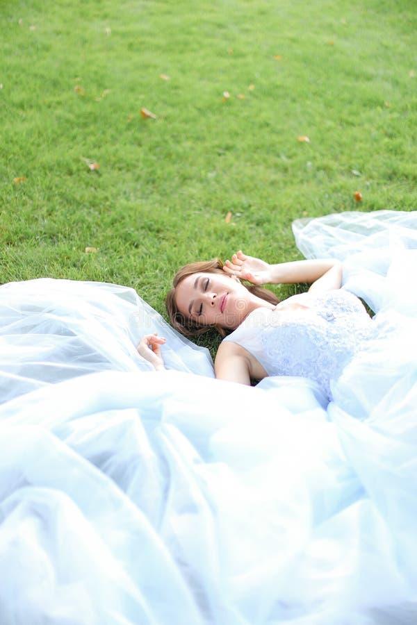 Oskyldig trevlig brud som ligger på gräs i oark och bärande vit klänning royaltyfri foto
