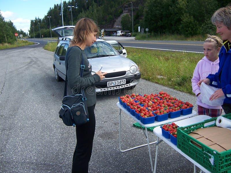 Oslo Norge - Juli 19, 2007: Den unga kvinnan köper jordgubbar i gatamarknaden royaltyfria foton