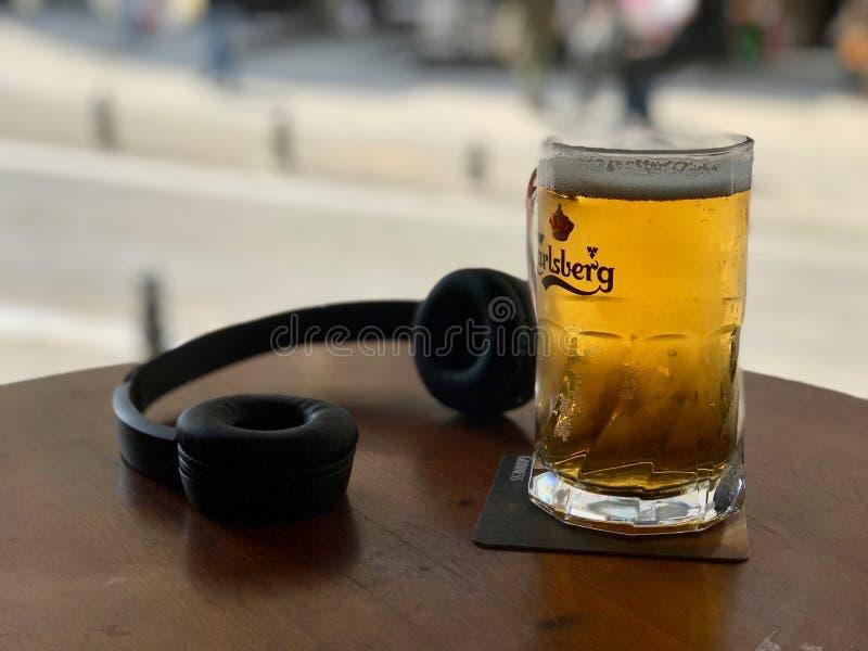 OSLO, NORWEGEN - CIRCA IM JULI 2015: ein Glas Carlsberg-Bier mit Kopfhörer, gebraut in Dänemark lizenzfreie stockbilder