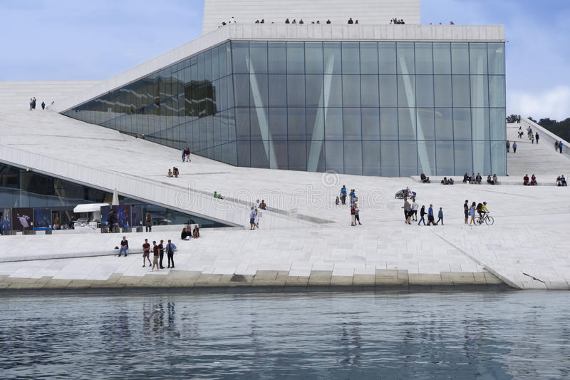 Oslo opera house with people and reflection. View of the grand opera building in Oslo, Norway. Reflected in water and with visitors admiring the architecture royalty free stock image