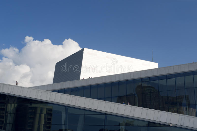 Oslo opera house with people and summer sky. View of the grand opera building in Oslo, Norway. Visitors admiring the architecture, set against a blue summer sky royalty free stock images