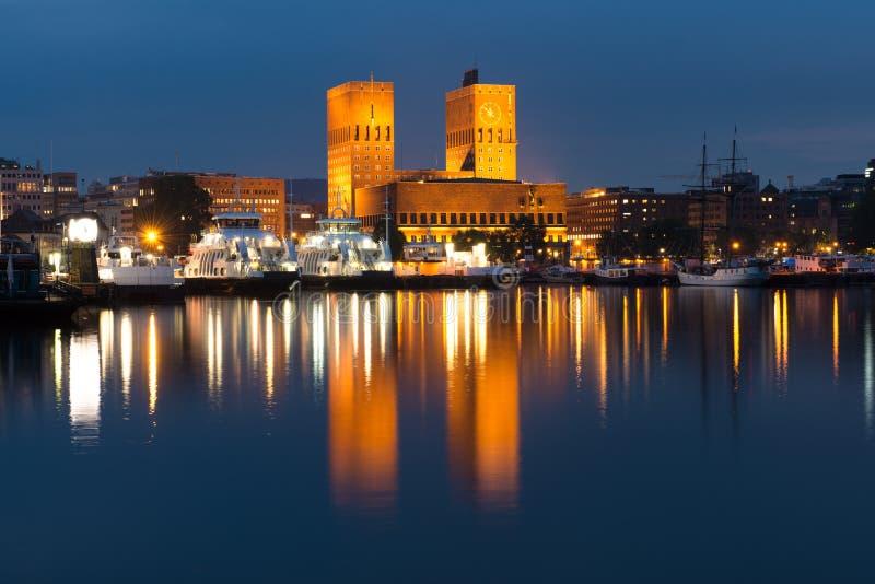 Oslo stadshus i natten med reflexionen i det glansiga vattnet arkivbilder