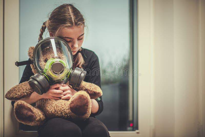 Oso De Juguete Con Máscara De Gas Abrazada Por Una Joven foto de archivo