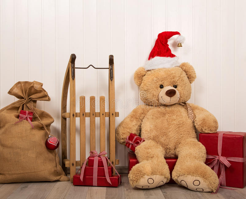 Oso de peluche como santa con un trineo de madera viejo y un christma rojo foto de archivo libre de regalías