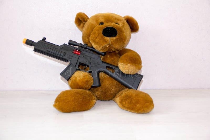 Oso de peluche con el arma del juguete el concepto de guerra, seguridad del niño, terrorismo, proteger a niños contra ataque arma imagen de archivo