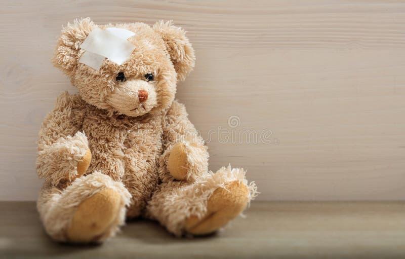 Oso de peluche con el vendaje en un piso de madera foto de archivo libre de regalías