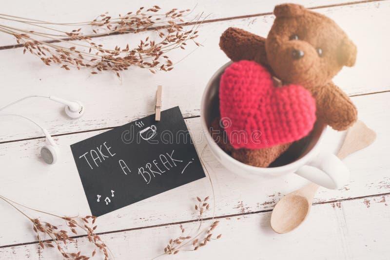 Oso de peluche con forma roja del corazón en la taza de café fotos de archivo libres de regalías