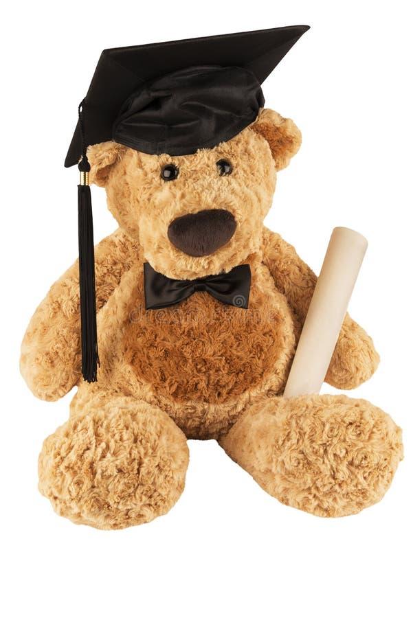 Oso de peluche con la corbata de lazo, el casquillo y el diploma aislados en el fondo blanco imagen de archivo