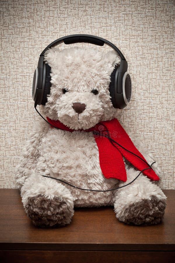 Oso de peluche con una bufanda roja que escucha la música en los auriculares imagenes de archivo