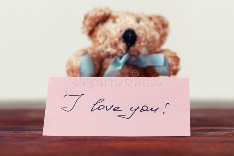 Oso de peluche con una nota que dice ` del ` te amo imagen de archivo libre de regalías