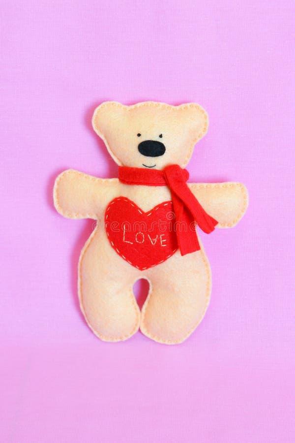Oso de peluche del fieltro del beige, juguete hecho a mano Juguete beige divertido del oso aislado en un fondo rosado de la tela fotografía de archivo libre de regalías
