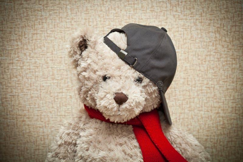 Oso de peluche en una bufanda roja y una gorra de béisbol negra imagen de archivo libre de regalías