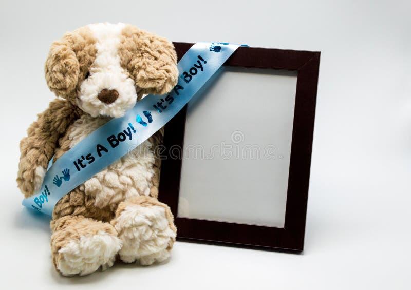 Oso de peluche de la felpa y marco vacío con el ` él ` s una cinta del ` del muchacho fotografía de archivo