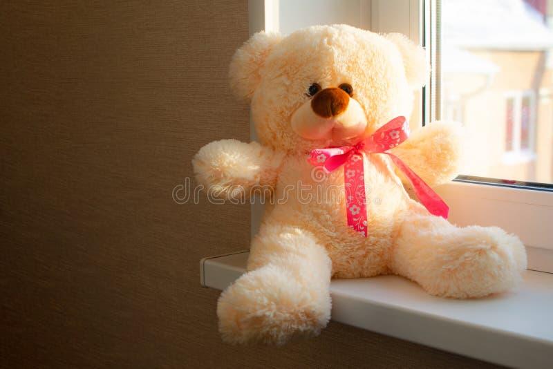 Oso de peluche lindo que mira fuera de la ventana Sensación de la muñeca sola Oso lindo que se sienta en la ventana Regalo del dí fotografía de archivo libre de regalías