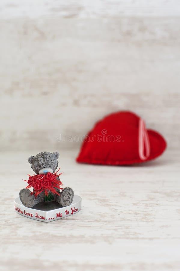Oso de peluche miniatura y corazón rojo en fondo de madera foto de archivo