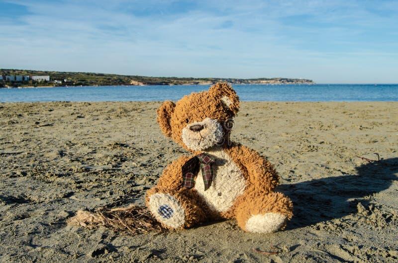 Oso de peluche que se sienta solamente en la arena en la playa - abandonada, el depresion, la violencia o el concepto de la peder imágenes de archivo libres de regalías