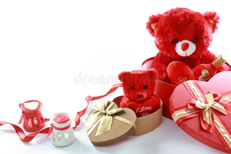 Oso de peluche rojo con el corazón rojo en caja de regalo en forma de corazón y cinta roja con la vela en el fondo blanco Día del fotos de archivo libres de regalías