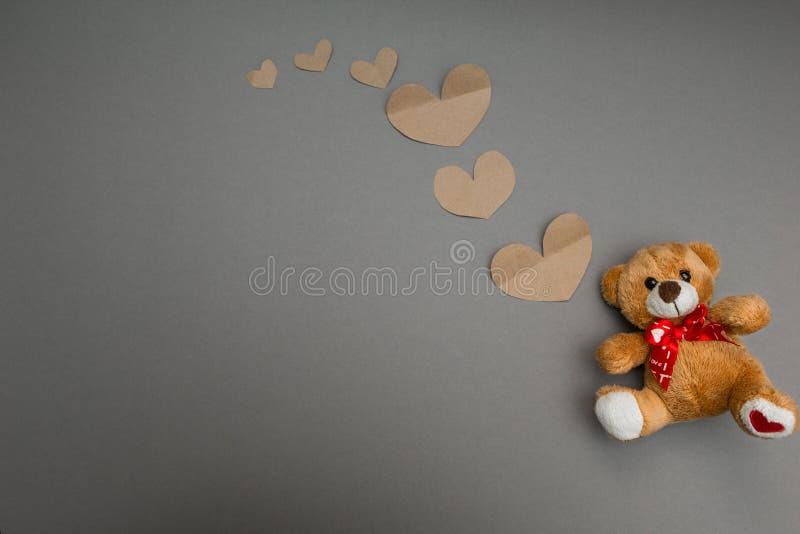 Oso de peluche y corazones de papel que vuelan en un fondo gris imagen de archivo