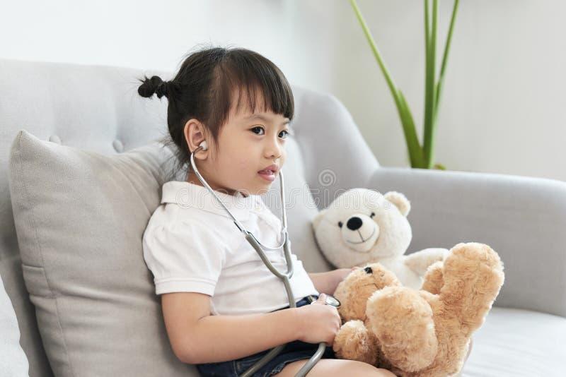 Oso el jugar y de la curación de una muchacha del doctor en el pediátrico fotografía de archivo libre de regalías