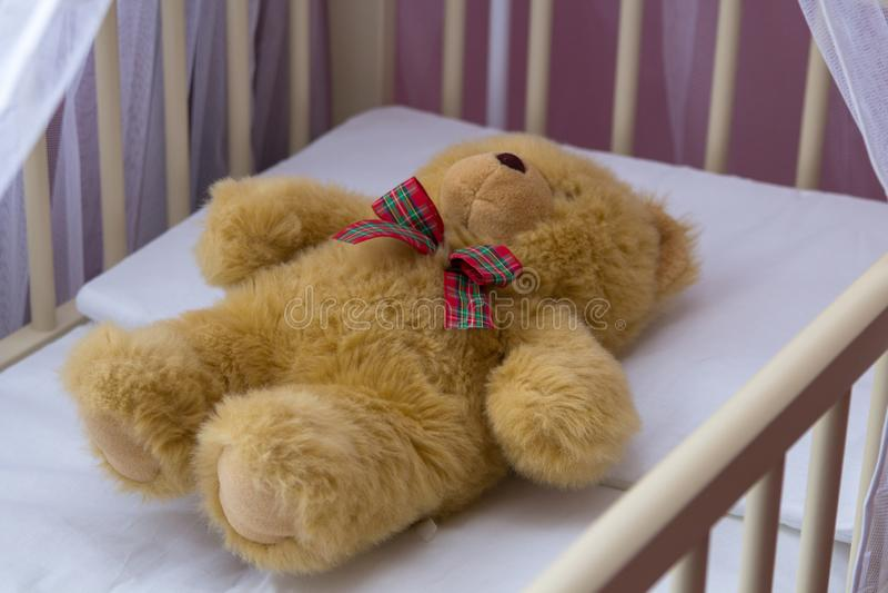 Oso en una cuna, un oso del juguete de peluche que duerme en un pesebre, un cuarto de ni?os imagenes de archivo