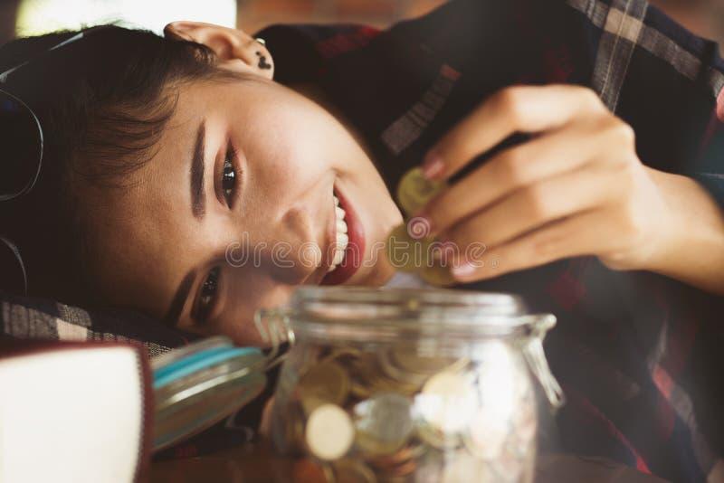 Osob ręki stawia pieniądze monety w szklaną butelkę zdjęcie royalty free