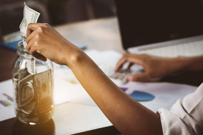 Osob ręki stawia pieniądze w szklaną butelkę fotografia royalty free