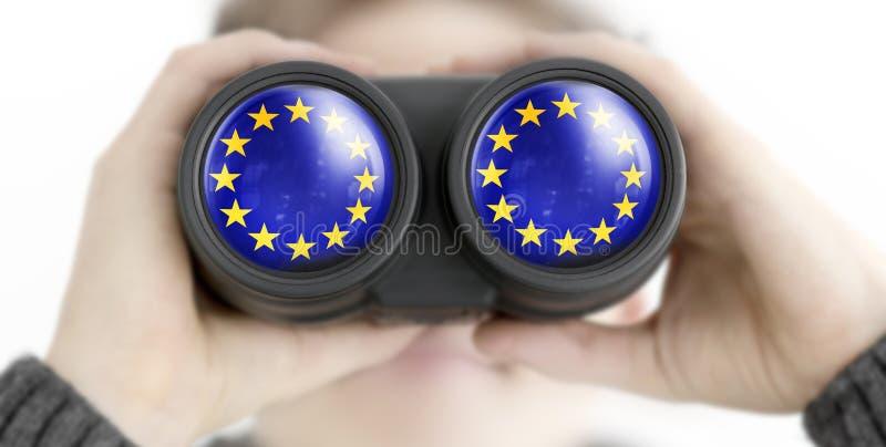 Osob spojrzenia przez lornetek z UE flag? fotografia royalty free
