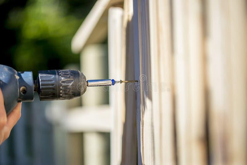 Osoba buduje drewnianego ogrodzenie z śrubą i świderem obrazy stock