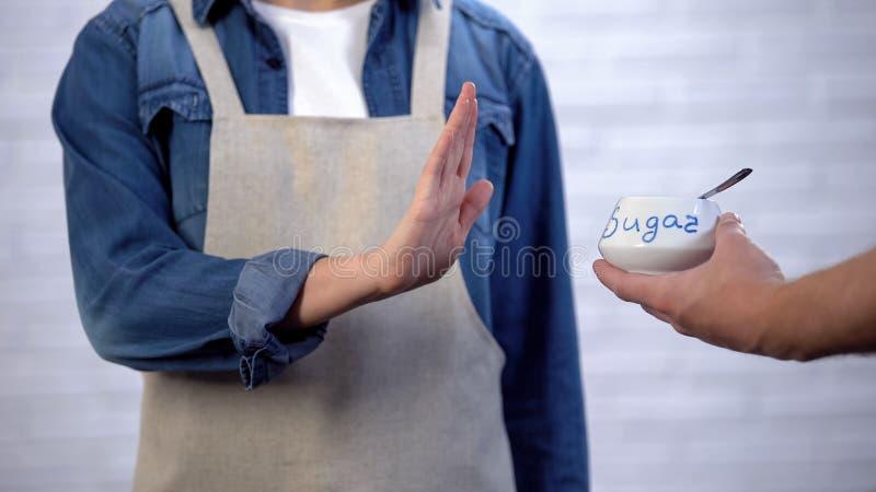 Osoba gestykuluje żadny cukier w kucharstwie, ryzyku cukrzyce i otyłości w fartuchu, fotografia stock