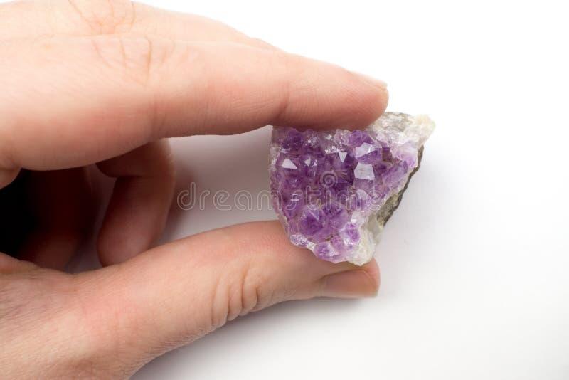 Osoba która trzyma palców kryształy purpurowy ametyst zdjęcie stock
