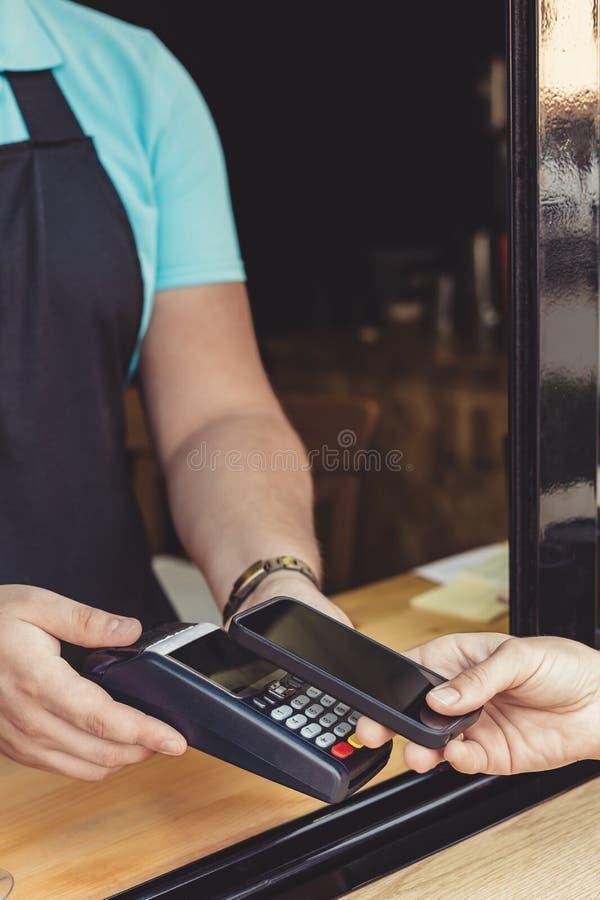 Osoba płaci wynagrodzenie przez smartphone używać NFC fotografia royalty free