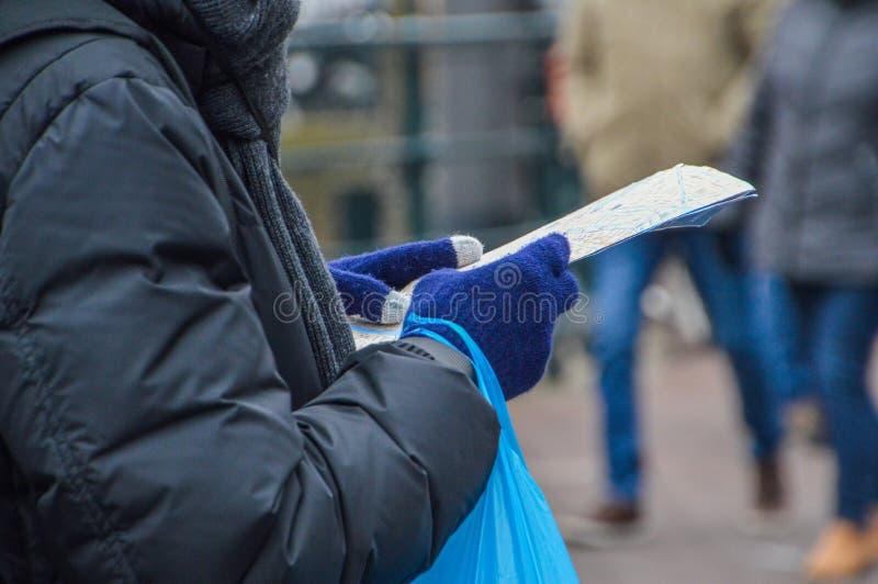 Osoba Patrzeje Amsterdam mapę Przy holandiami 2018 zdjęcia stock