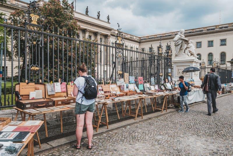Osoba patrzeje drugi rękę rezerwuje dla sprzedaży na pchli targ przed Humboldt uniwersytetem w Berlin zdjęcia stock