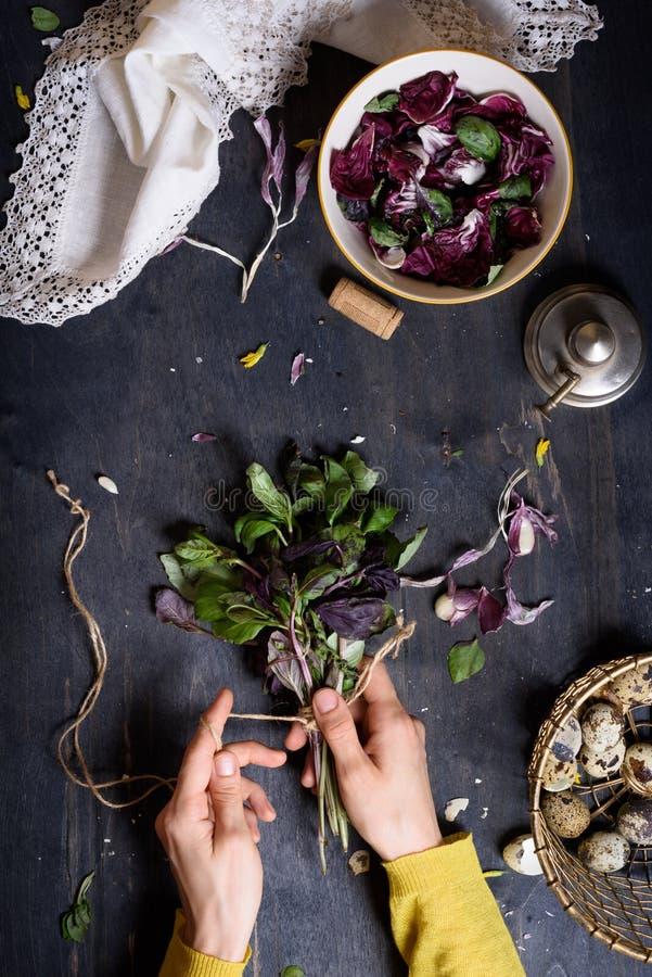 Osoba przygotowywa zdrowej ziołowej sałatki z basilu, radicchio i przepiórki jajkami, Nieociosany drewniany stół, widok od above zdjęcia royalty free