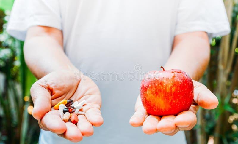 Osoba trzyma czerwonego jabłka w jeden ręce i garść pigułek w inny zdjęcia stock